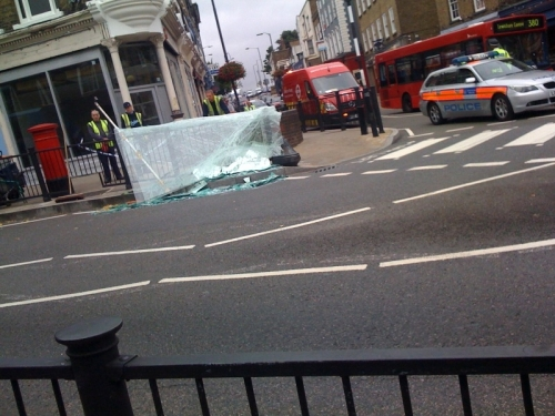 Pane of glass, police blocking the traffic on the road, blackheath