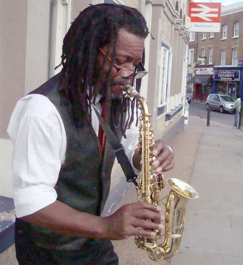 Saxophonist busker playing his sax outside Blackheath Station on a Sunday. Photo by Flickr user Julie70.